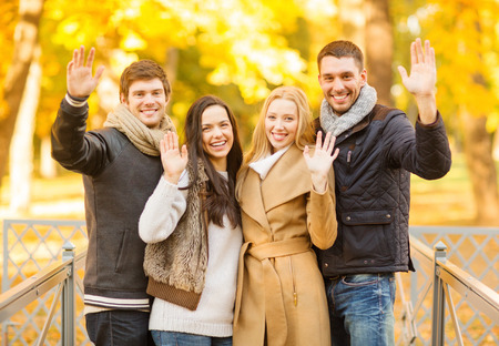 summer, holidays, vacation, happy people concept - group of friends or couples having fun and waving hands in autumn park photo