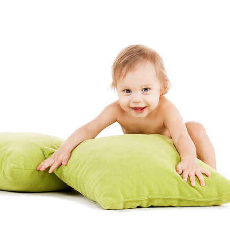 childhood and toys concept - cute little boy playing with green pillows Stock Photo - 23436426