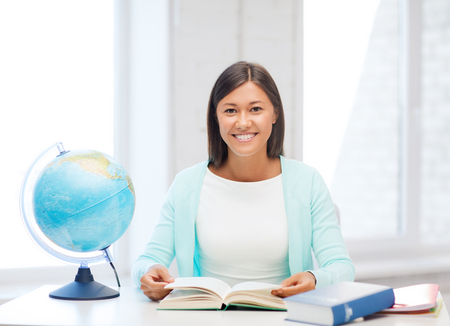 education and school, travel concept - female teacher with globe and book photo
