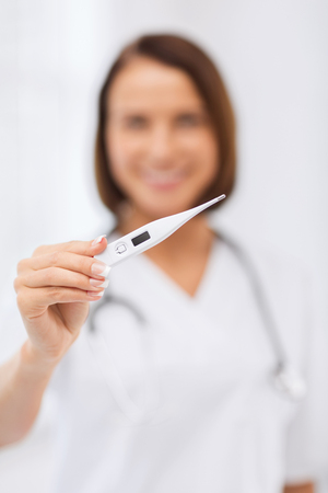 healthcare and medical concept - female doctor with thermometer and stethoscope photo