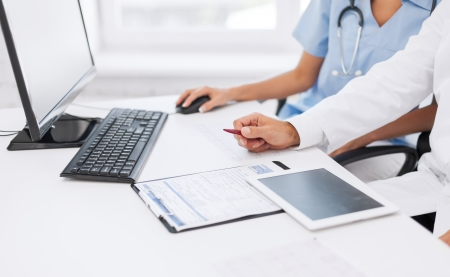 healthcare: healthcare, medical and technology concept -  group of doctors looking at tablet pc