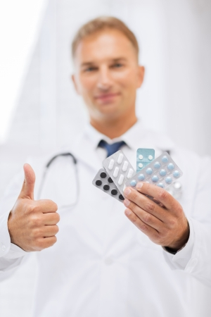 healthcare, medical and pharmacy concept - male doctor with packs of pills showing thumbs up photo