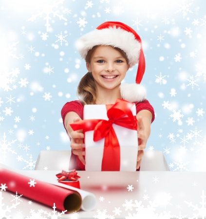 christmas, x-mas, winter, happiness concept - smiling girl in santa helper hat with gift box photo