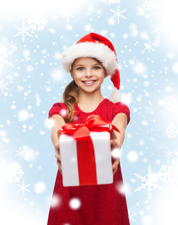 christmas, x-mas, winter, happiness concept - smiling girl in santa helper hat with gift box Stock Photo