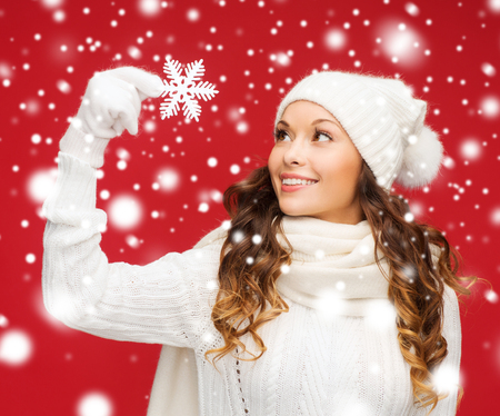 winter woman: winter, people, happiness concept - woman in hat, muffler and gloves with big snowflake Stock Photo