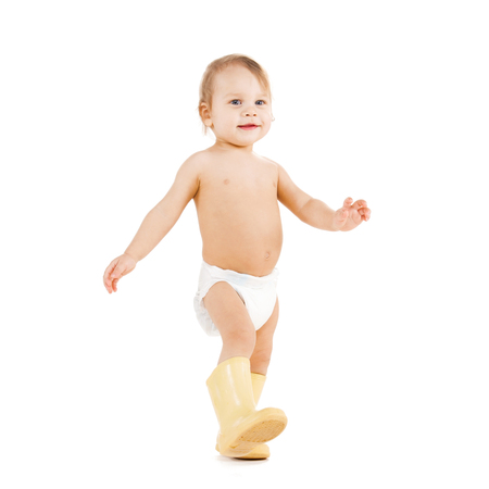 childhood and toys concept - cute little boy walking in big rubber boots photo