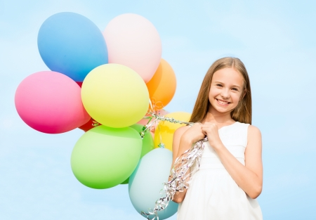 summer girl: summer holidays, celebration, family, children and people concept - happy girl with colorful balloons