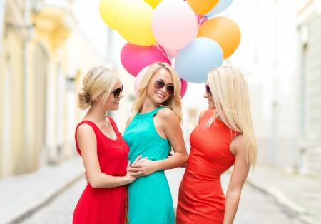 holidays and tourism, friends, hen party, blonde girls concept - three beautiful women with colorful balloons in the city photo