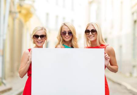 bachelorette party: summer holidays, , travel, tourism and advertisement concept - three happy blonde women with blank white board in the city