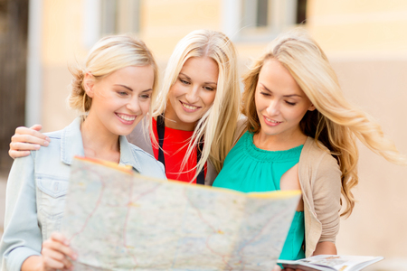 holidays and tourism concept - beautiful blonde women with tourist map in the city photo
