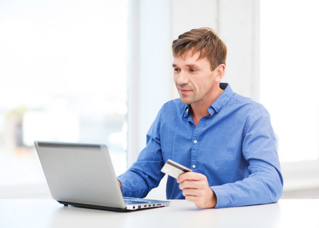 business, online banking, internet shopping concept - smiling man with laptop and credit card at home Stock Photo - 23437225