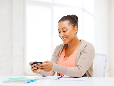 business, and communication concept - smiling african woman with smartphone in office photo