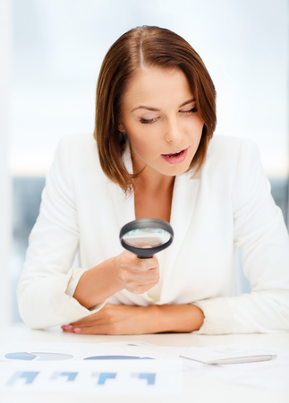 business, education, school, documents, people concept - businesswoman or student in eyeglasses working with graphs in office photo