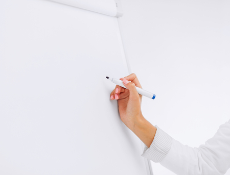 business, office, school and education concept - businesswoman working with flip board in office photo