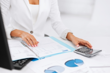 secretary woman: business, office, tax, school and education concept - woman hand with calculator and papers