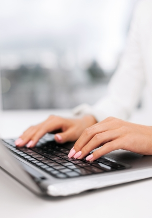office, business, technology and internet concept - businesswoman using her laptop computer photo