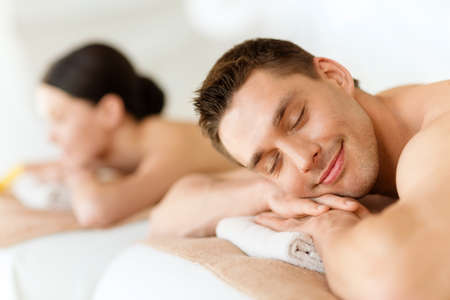 health and beauty, resort and relaxation concept - couple in spa salon lying on the massage desks photo
