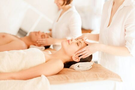 health and beauty, resort and relaxation concept - couple in spa salon getting facial massage photo