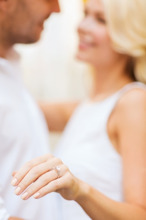 summer holidays, love, travel, tourism, relationship and dating concept - romantic man proposing to beautiful woman photo