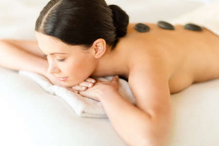 health and beauty, resort and relaxation concept - woman in spa salon with hot stones photo