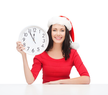 christmas, x-mas, winter, happiness concept - smiling woman in santa helper hat with clock showing 12 Stock Photo - 23437363
