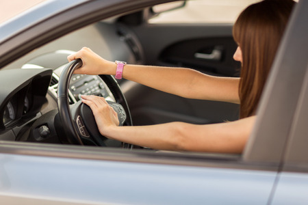 transportation and vehicle concept - woman driving a car with hand on horn button Imagens
