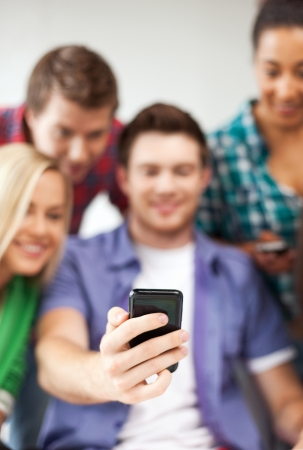 taking photograph: education and internet - smiling students looking at smartphone