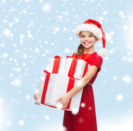 christmas, x-mas, winter, happiness concept - smiling girl in santa helper hat with many gift boxes photo