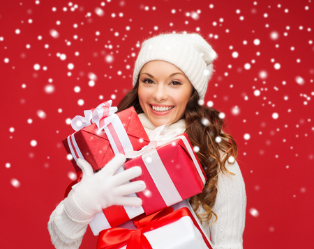 christmas, x-mas, winter, happiness concept - smiling woman in sweater and hat with many gift boxes photo