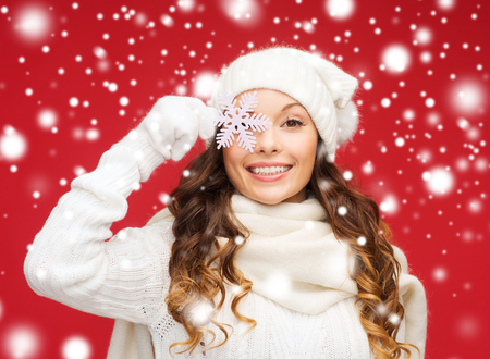 winter, people, happiness concept - woman in hat, muffler and gloves with big snowflake photo