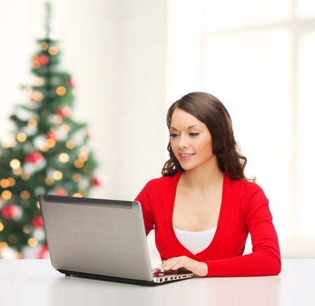 christmas, x-mas, electronics, gadget concept - smiling woman in red clothes with laptop computer photo