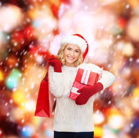 christmas shopping: shopping, sale, gifts, christmas, x-mas concept - smiling woman in santa helper hat with shopping bags and gift boxes