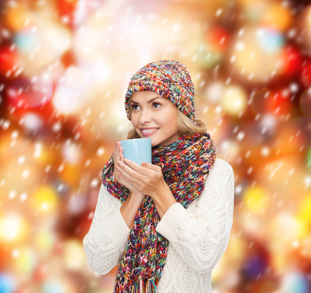 winter, people, happiness, drink and food concept - woman in hat with red tea or coffee mug looking up photo