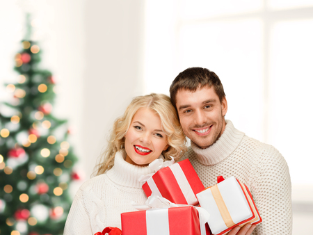 christmas, x-mas, winter, valentines day, birthday, couple, happiness concept - smiling woman and man with many gift boxes photo