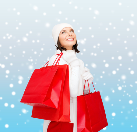 christmas spending: retail and sale concept - happy woman in winter clothes with shopping bags Stock Photo