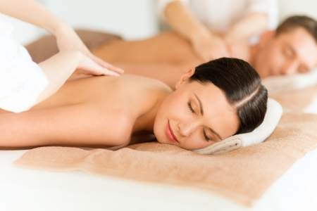 health and beauty, resort and relaxation concept - couple in spa salon getting massage photo
