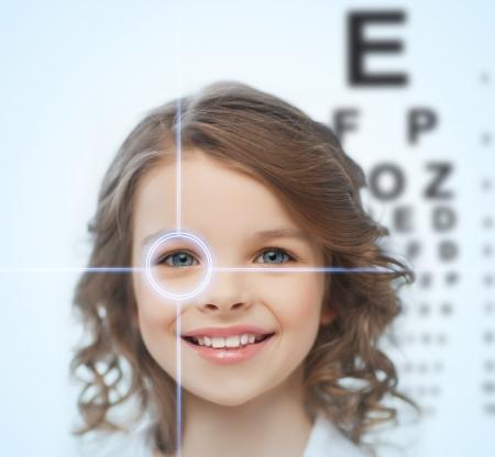 gezondheid, visie, geneeskunde, laser correctie, gelukkige mensen concept - lachend pre-tiener meisje met optometric tafel of gezichtsvermogen testen boord Stockfoto