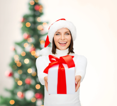 santa helper: christmas, x-mas, winter, happiness concept - smiling woman in santa helper hat with gift box