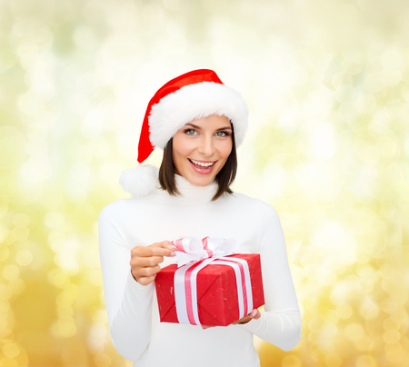 christmas, x-mas, winter, happiness concept - smiling woman in santa helper hat with gift box photo