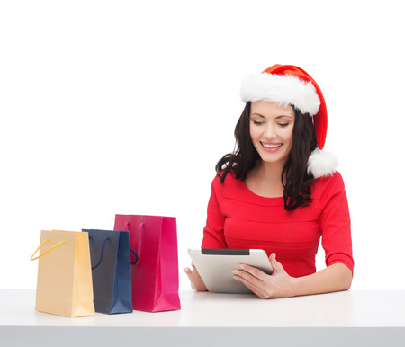 christmas, x-mas, online shopping concept - woman in santa helper hat with gift box and tablet pc computer photo