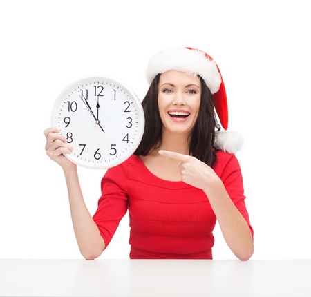 christmas, x-mas, winter, happiness concept - smiling woman in santa helper hat with clock showing 12 Stock Photo - 23437685