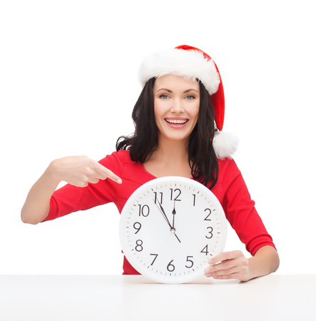 christmas, x-mas, winter, happiness concept - smiling woman in santa helper hat with clock showing 12 Stock Photo - 23437686
