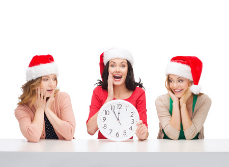 christmas, x-mas, winter, happiness concept - three smiling women in santa helper hats with clock showing 12 Stock Photo - 23437690