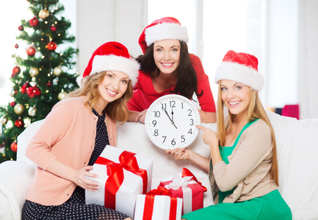 christmas, x-mas, winter, happiness concept - three smiling women in santa helper hats with clock showing 12 and gift boxes Stock Photo - 23437699