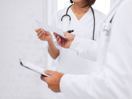 healthcare and medical concept - two doctors writing prescription Stock Photo - 23671574
