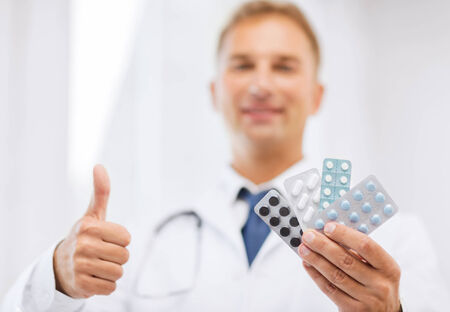 packs of pills: healthcare, medical and pharmacy concept - male doctor with packs of pills showing thumbs up Stock Photo