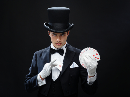 trick: magic, performance, circus, gambling, casino, poker, show concept - magician in top hat showing trick with playing cards Stock Photo