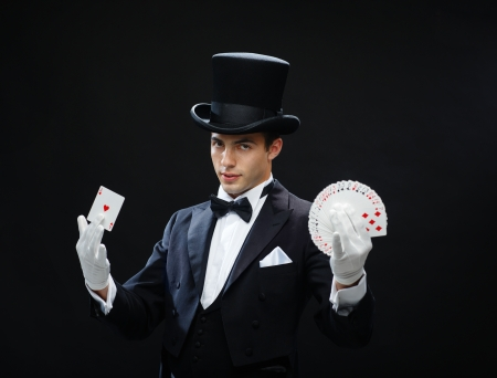 magician hat: magic, performance, circus, gambling, casino, poker, show concept - magician in top hat showing trick with playing cards Stock Photo