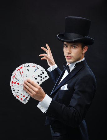 magic, performance, circus, gambling, casino, poker, show concept - magician in top hat showing trick with playing cards Zdjęcie Seryjne