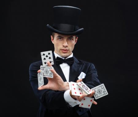 magie, prestaties, circus, het gokken, casino, poker, showconcept - tovenaar in hoge hoed met truc met speelkaarten Stockfoto